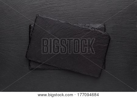 Two black slate boards on dark textured background