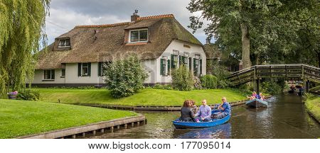 GIETHOORN, NETHERLANDS - AUGUST 9, 2016: Panorama of tourists in an electric boat in the canals of Giethoorn, Holland