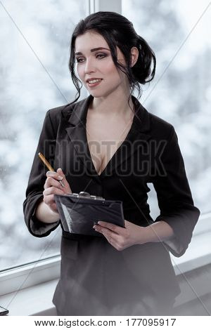 Beautiful sexy business woman with a clipboard in office