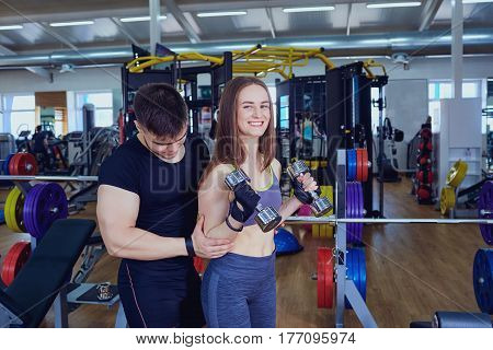 Personal trainer helps sports girl doing exercises with dumbbells in the gym.