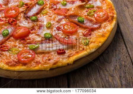 Italian pizza with chili peppers on wood background, closeup