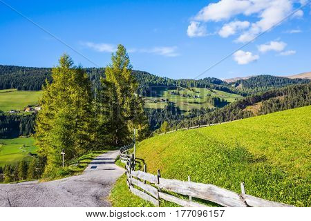 The forested mountains surrounded by green Alpine meadows. The road descends into the Val de Funes. Warm autumn in the Dolomites. The concept of ecological tourism