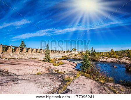 Old Pinawa Dam Park. The ruins of the old dam. Indian summer in Manitoba, Canada. The concept of ecological and recreational tourism. Clouds and autumn sun over river Winnipeg