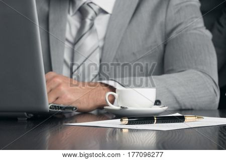 Close up of business man working with documents and laptop in office