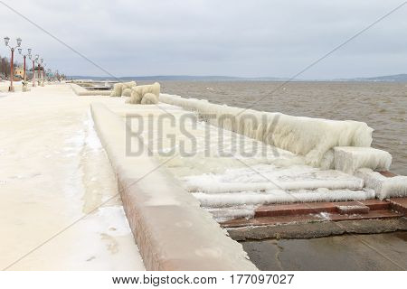 City embankment covered with ice after winter storm on the lake. Onega lake, Petrozavodsk, Russia