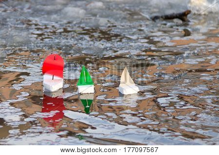Children's toy boats floating in water outdoors in springtime