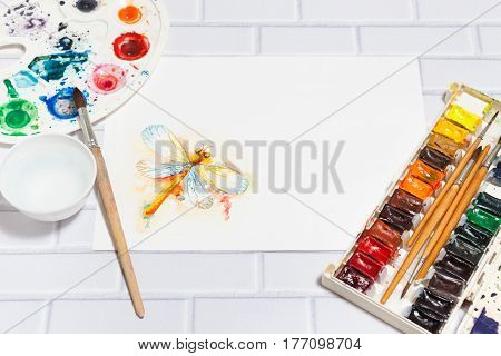 Hand Drawn Sketch of Orange Dragonfly with lying paints paintbrushes and palette on the white brick background - concept of human creativity perspective view. Have an empty place for your text