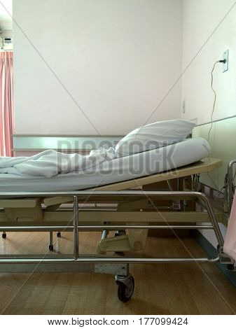Patient's empty bed in a hospital room.