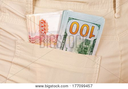 Heap banknotes of american dollars and russian rubles in the back jeans pocket