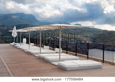 Place sun with sun beds and umbrellas on the background of mountains and gloomy clouds