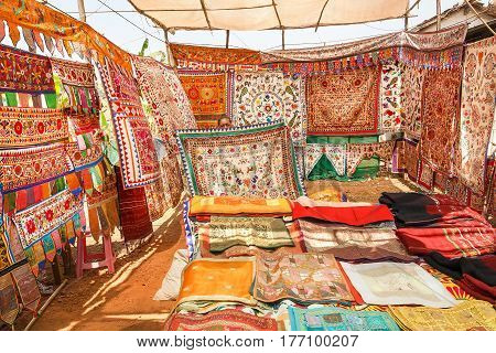 GOA, INDIA - MAR 1, 2017: Seller of antique carpets shows colorful embroidered bedspreads at the marketplace of oriental bazaar on March 1, 2017. Near 5 million tourists visit Goa annually
