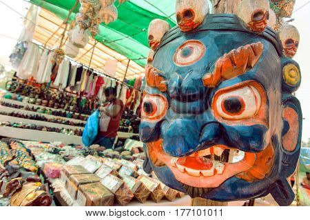 GOA, INDIA - MAR 1, 2017: Indian souvenir market with old wooden mask of Mahakala deity popular in Hinduism and Buddhism on March 1, 2017. Near 5 million tourists visit Goa annually