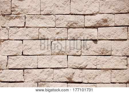 A fragment of a wall made of rough gravel bricks