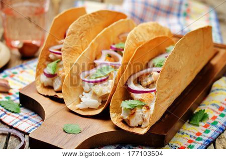 Rice chicken cilantro tacos on wood background.