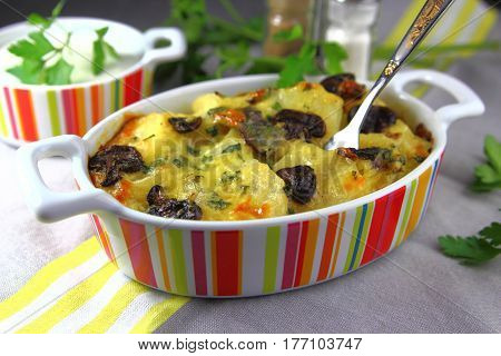 potato casserole with mushrooms,cheese and parsley in a ceramic baking dish