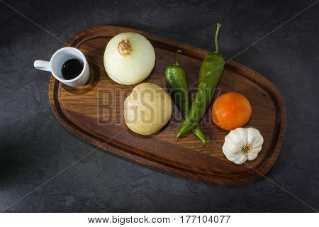 Assorted vegetables including an onion, chili's, tomato, garlic loaf and a cup of black liquid on a wooden tray.