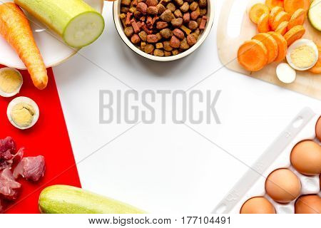 healthy dry dogfood with cut ingredients on kitchen table background top view mock up