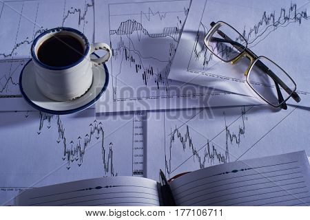 On the table are charts of quotations with various indicators a cup of coffee a notebook a pen and glasses