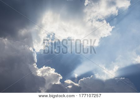 Amazing blue sky with clouds and streams of sunlight.