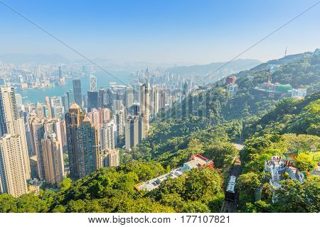Aerial view of popular Peak Tram, Lion's Pavilion terrace and Hong Kong cityscape from Victoria Peak, the highest peak of Hong Kong island.
