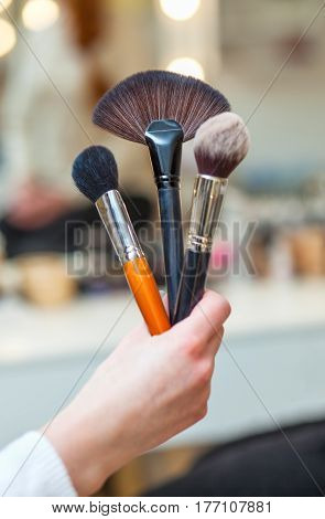 The Make-up Artist Holds In His Hand Three Brushes Made Of Natural Bristles For Powder, Foundation A