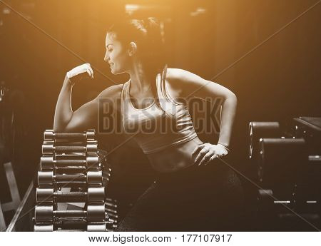 Slim bodybuilder girl shows biceps while training in the gym. Sports concept fat burning and a healthy lifestyle.