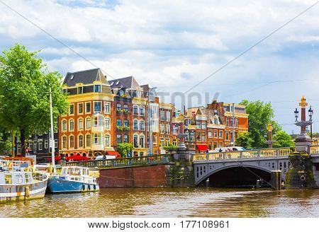 Beautiful cityscape of Amsterdam capital of Netherlands. Colorful view of the Amstel river with an amazing Blauwbrug Blue Bridge and building in summer day. Horizontal Image