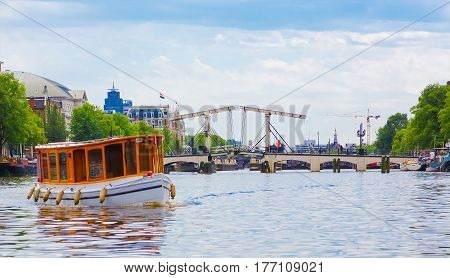 Beautiful panoramic View of the canal with a drawbridge in Amsterdam Netherlands. Colorful cityscape. Horizontal Image