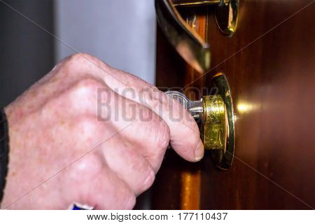 Male hand opens the door with a key
