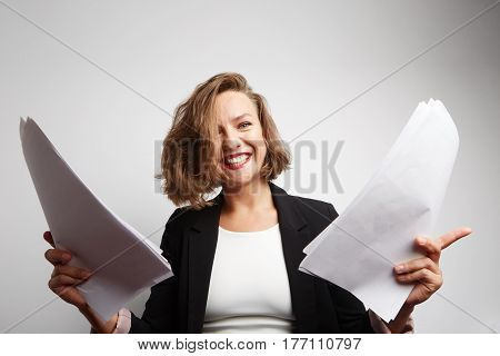 Perplexed accountant doing financial reports holding documents.