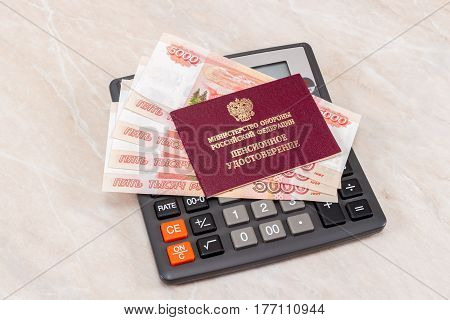 MOSCOW RUSSIA - JANUARY 6 2017: Russian Military Pension Certificate with money lying over calculator. Text in russian: