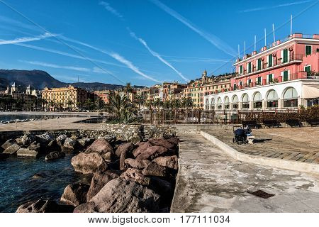 SANTA MARGHERITA LIGURE, ITALY - DECEMBER 2016: Woman with baby carriage is sitting at promenade near coastline of Santa Margherita town in Italy