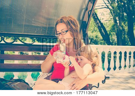Mother And Daughter Having Breakfast Outdoors.