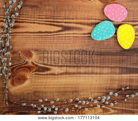 Happy easter. Easter background. Easter cookies. Gingerbread in the form of colored Easter eggs and willow branches on a background of brown wooden desk. Free space