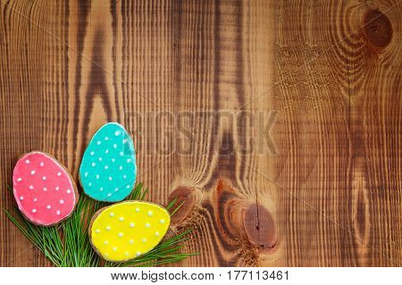 Happy easter. Easter background. Easter cookies. Gingerbread in the form of colored Easter eggs on green grass on a background of brown wooden desk. Free space