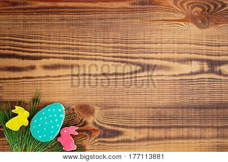 Happy easter. Easter background. Easter cookies. Gingerbread in the form of colored Easter rabbits and eggs on green grass on a background of brown wooden desk. Free space
