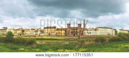 Beautiful panoramic view of Flornce riverside Arno River National Library in the middle green grass in foreground and majestic powerful cloudy sky