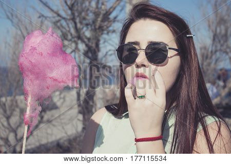 Pretty Young Woman With Dark Long Hair And Blue Eyes Walking On The Harbour, Eats Pink Candy Cotton