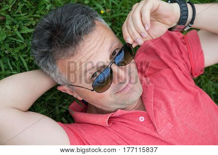 Portrait of handsome happy mid-adult man posing in sunglasses on summer meadow in green grass.