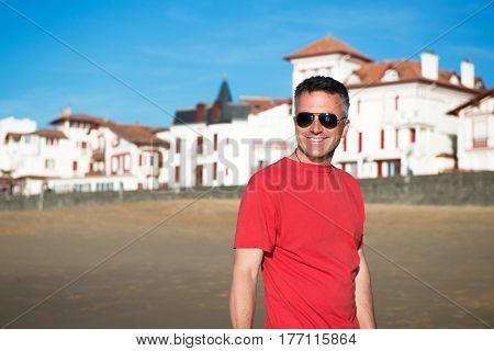 Handsome man. Outdoor male portrait. Happy middle-aged man resting at the beach, summer outdoor portrait, image toned. Saint Jean de Luz, France.