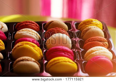 traditional french colorful macarons in a rows in a box.