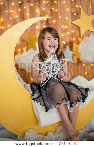 Beautiful baby girl 5-6 year old sitting on a wooden month with a decorative star in her hands. Children's photozone.