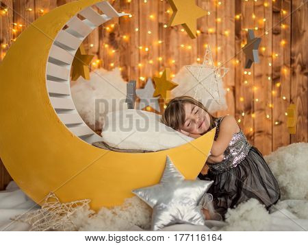 Beautiful kid girl 5-6 year old sitting smiles in a dream on a wooden month. Children's photozone. Childhood.