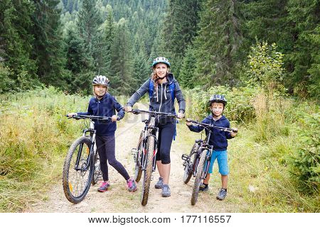 Young woman with her son and daughter enjoying cycling in forest. Family riding bike concept background