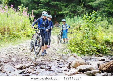 Young woman with her children on bikes wade the mountain creek