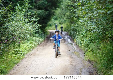 Small boy in helmet riding the bicycle on mountain road