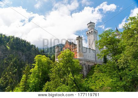 The magnificent New Swan Stone Castle - Schloss Neuschwanstein perched on a cliff surrounded in Schwangau, Bavaria, Germany