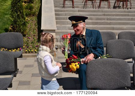 PYATIGORSK RUSSIA - MAY 09 2011: Girl gives flowers to veteran on Victory Day. 9 may