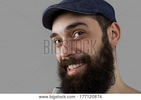 Close up portrait of happy and smiling bearded man in studio on grey background. Male have interesting and adventure life like to travel and extreme hiking.