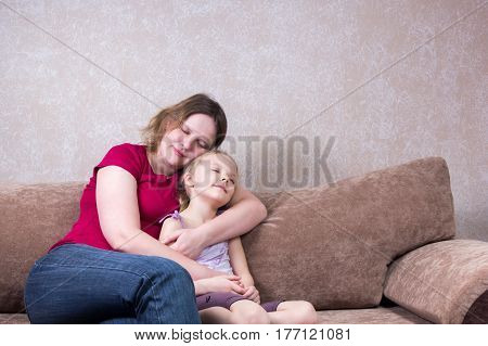 Mother Hugs Her Daughter On Couch